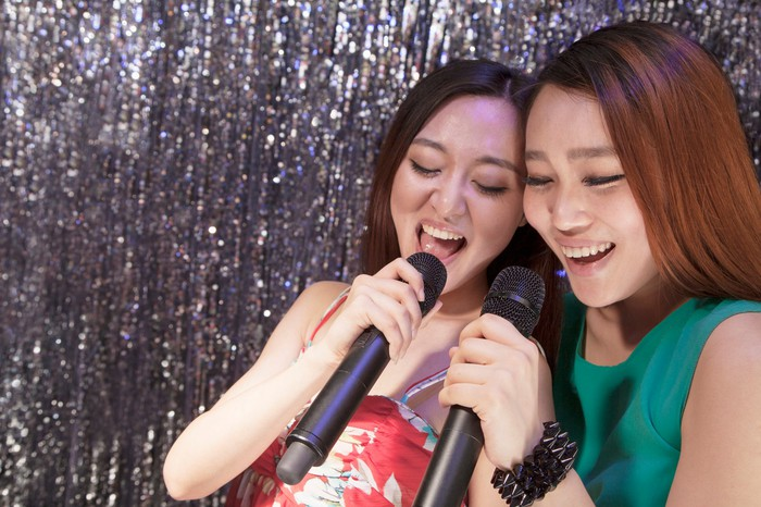 Two women sing karaoke together.