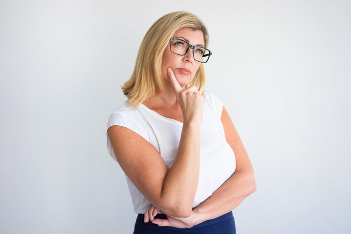 A woman in glasses ponders a decision.