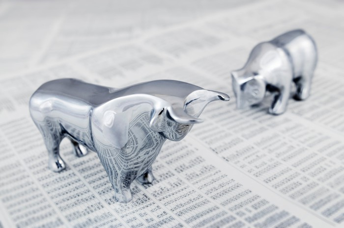 Chrome bull and bear figurines standing on top of a newspaper with stock market data.