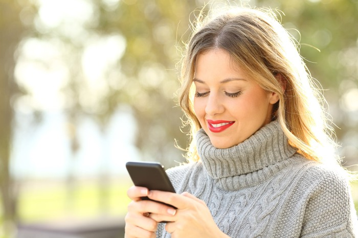 Young woman smiling while looking at cell phone.