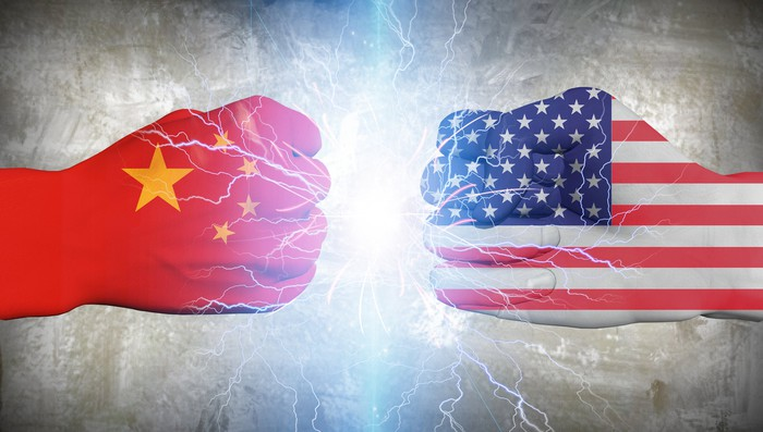 Two fists, one painted as a Chinese flag, the other as an American flag.