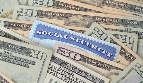 Social Security card in a pile of cash_GettyImages-178491316