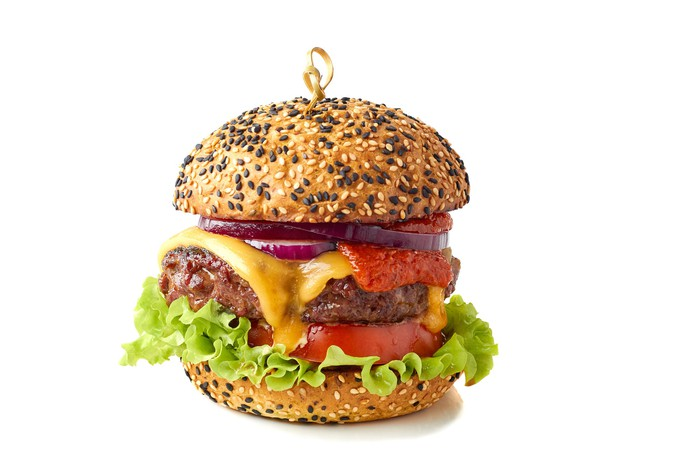 A hamburger on sesame buns, stuffed with lettuce, tomato, cheese, and onions