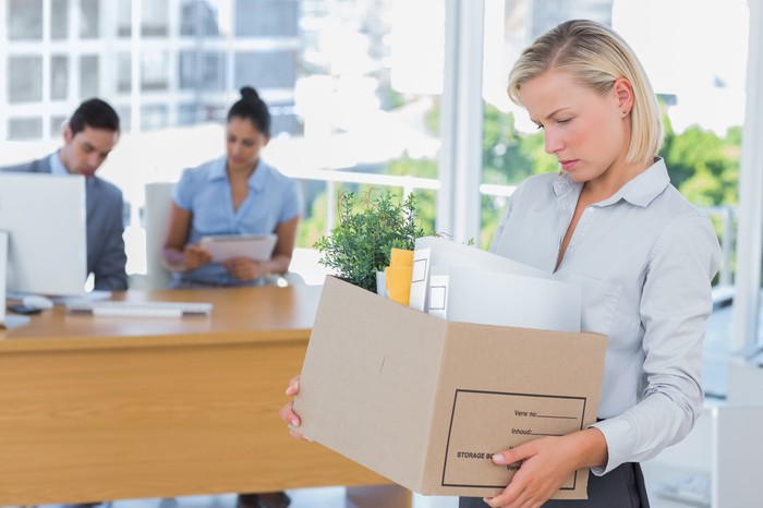 Woman with sad expression carrying cardboard box out of an office.