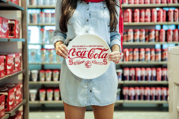 Woman holding plate in Coca-Cola store