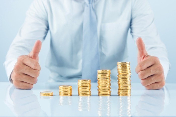A businessman giving the thumbs-up sign with a growing stack of coins in front of him.