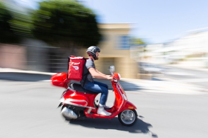 A DoorDash driver making a delivery on a red DoorDash scooter.