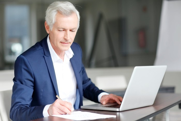 Older man in collared shirt and jacket taking notes while typing on laptop