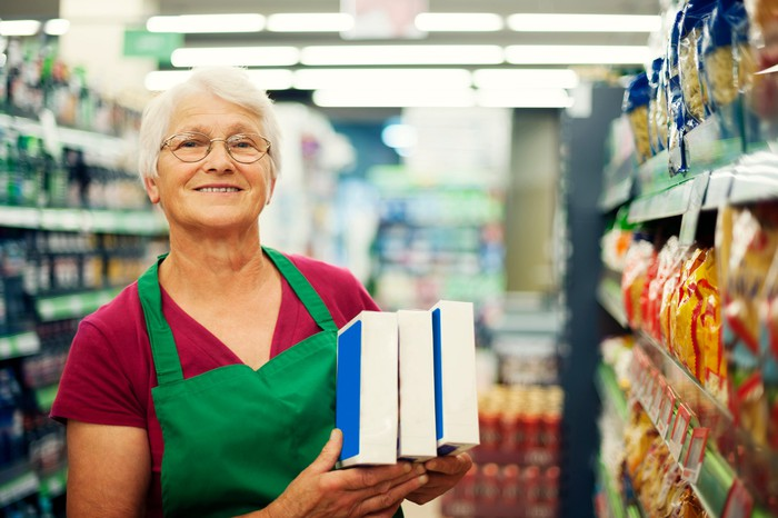 Older woman in a green apron working at grocery store stocking shelves.