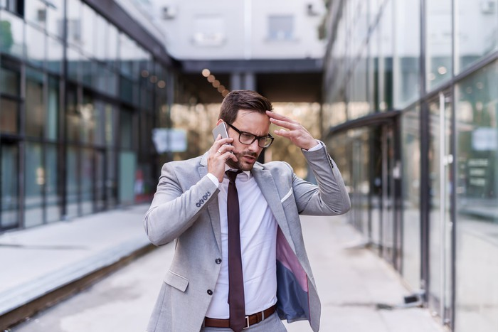 Man in business suit talking on phone outdoors and holding head