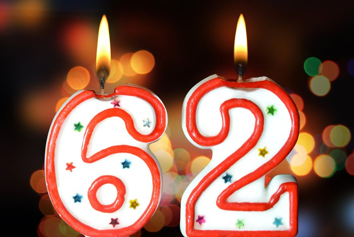 Two big birthday candles are shown, lit -- one if the number six and the other a 2, making 62.
