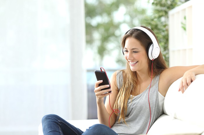 A smiling woman sits on a couch, wearing headphones and looking at her smartphone.