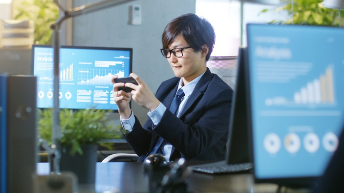 A businessman plays a mobile game at work.