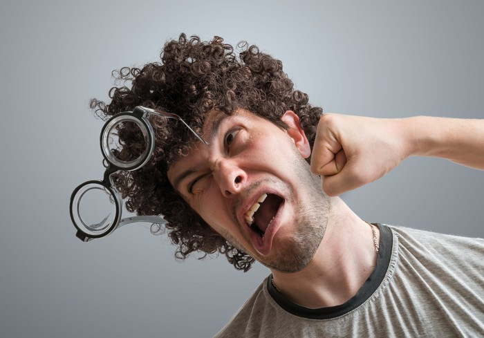 A white man with curly hair and glasses getting punched in the face.