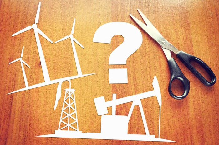 Paper cutouts of wind turbines, an old oil well, and a question mark.