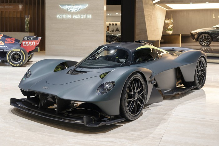 A gray Aston Martin Valkrye, a low-slung mid-engined sports car, shown on Aston Martin's show stand at the 2019 Geneva Motor Show.
