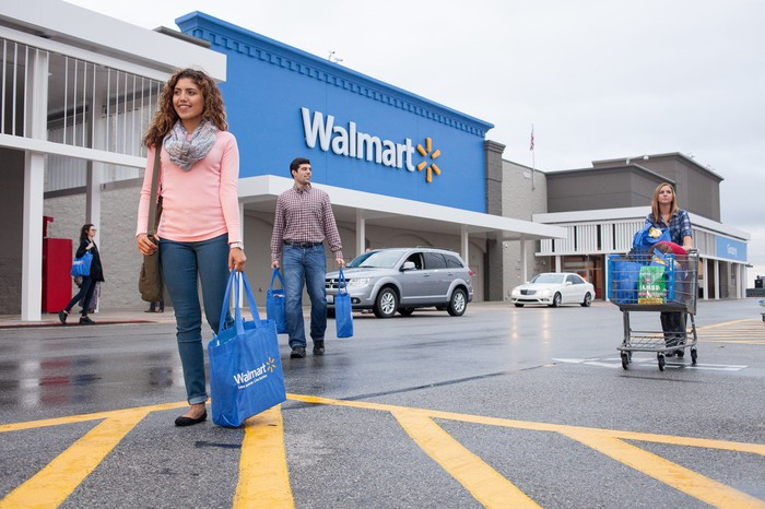Three people walking across a parking lot in front of a Walmart store, with some cars nearby.