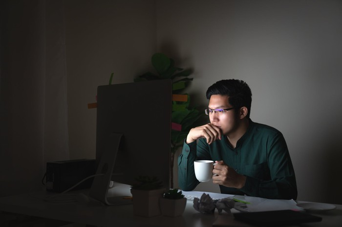 An Asian man sitting at his laptop in the dark, holding a mug of tea or coffee