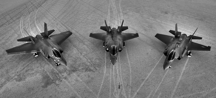 Three F-35 Joint Strike Fighters parked on a runway