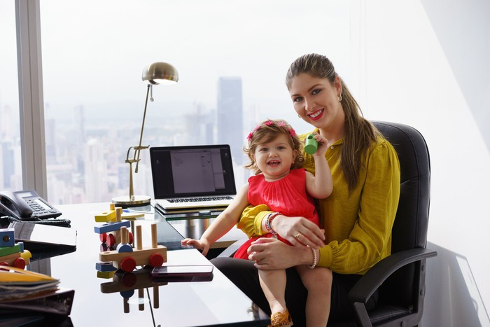 A working mom sits at her office desk with her toddler in her lap.