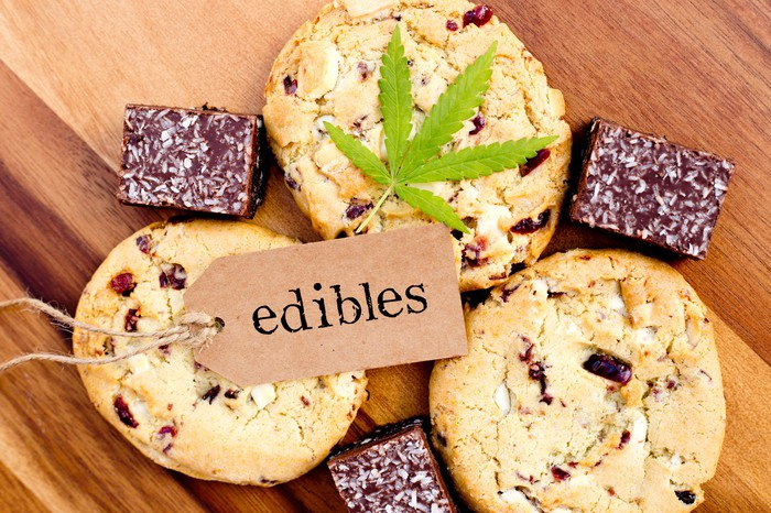 A dog tag with the word edibles lying atop cookies and brownies, with a single cannabis leaf set atop one of the cookies.