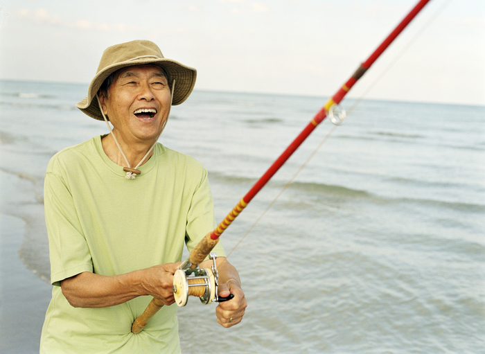 Laughing older man holding red fishing pole, wading in the waves.