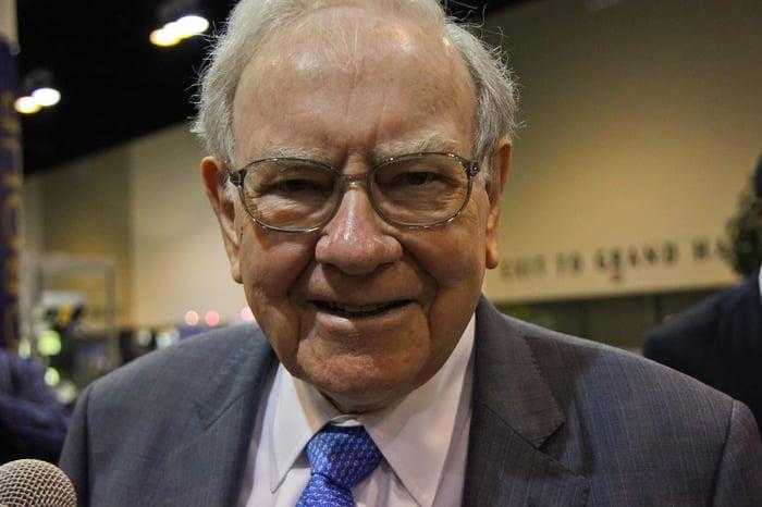 Warren Buffett smiling at the camera.