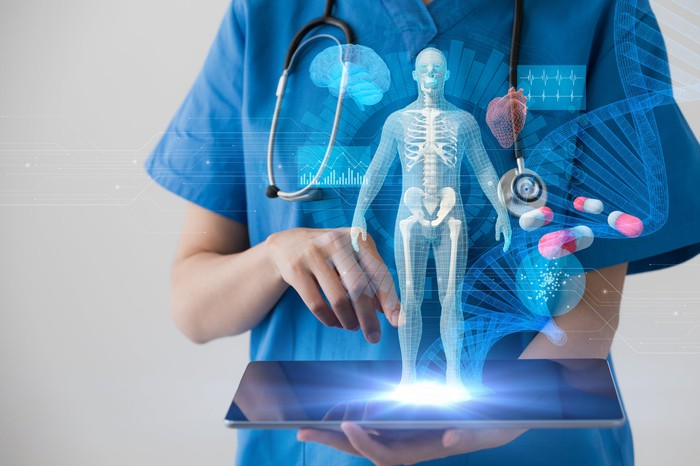 A doctor in scrubs holding a tablet that's projecting a holographic image of a transparent human body.