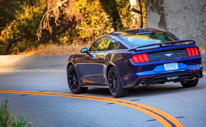 Blue Ford Mustang rounding a corner on gray asphalt with bushes along the roadside.