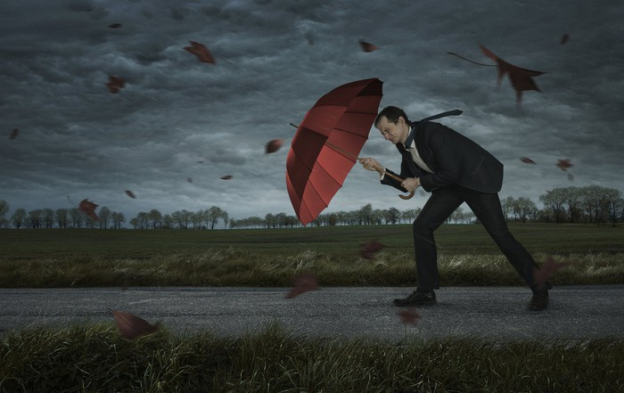 Man in suit pushing against wind with umbrella, with dark clouds in the background.