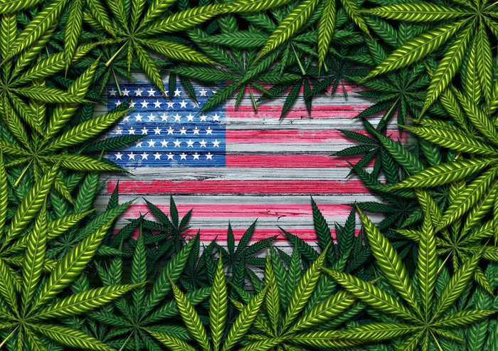 Rustic U.S. flag framed by a pile of marijuana leaves.