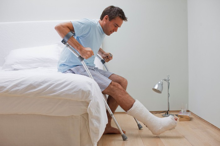 Man sitting on edge of bed with leg in cast, trying to hoist himself up with crutches
