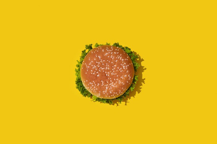 A burger on a bright yellow surface