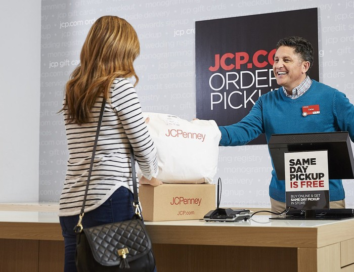 Person behind counter giving J.C. Penney bag to customer.