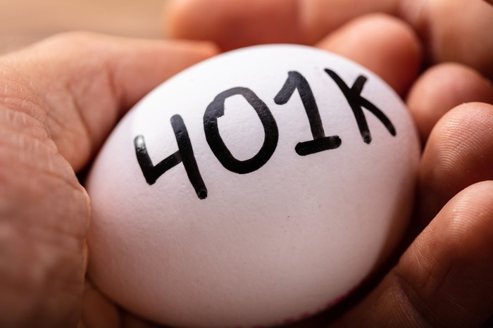 A white egg in the palm of a hand, with 401k written on it.