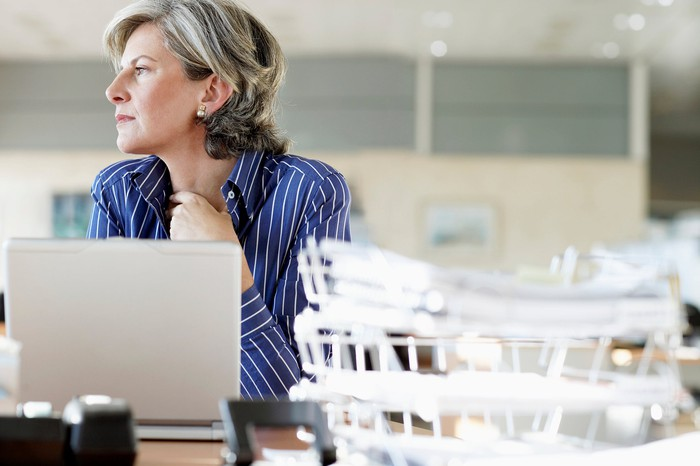Older woman at laptop, deep in thought