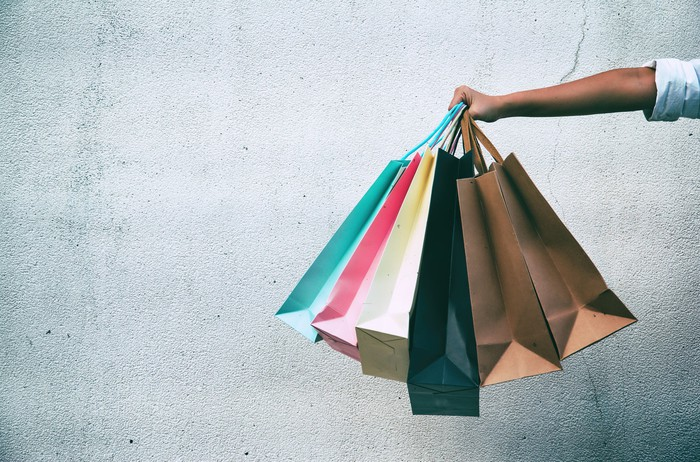 A woman holds out several shopping bags.