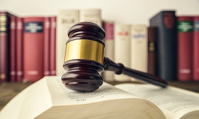 Gavel on an open lawbook on a desk with other books in the background.
