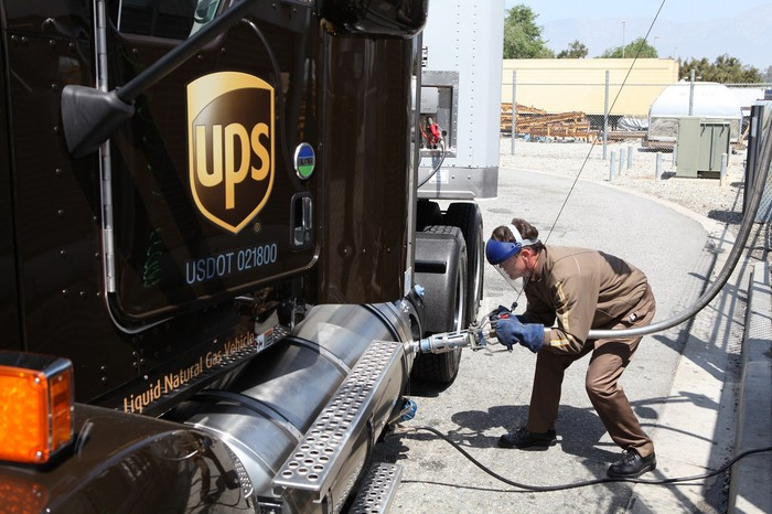 UPS worker pumping LNG into a semi truck.
