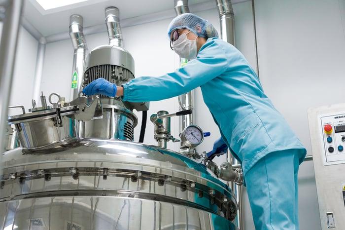 A technician checking a bioreactor.