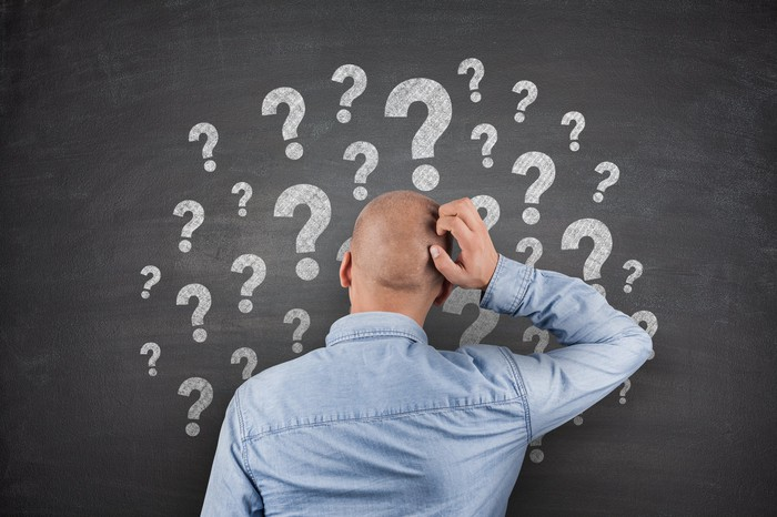 Man scratches head while looking at chalkboard with question marks on it.