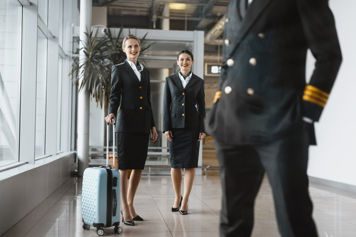 Flight attendants looking at a pilot