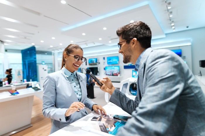 A man looking at a phone being shown to him by a female employee in an electronic store.