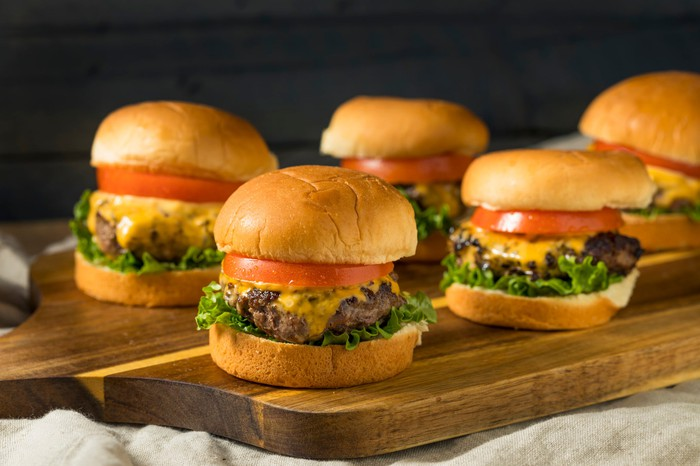 Burgers on a cutting board.