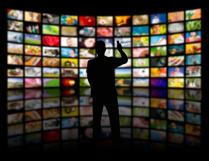 A man in silhouette with a remote facing a wall of dozens of TV screens.