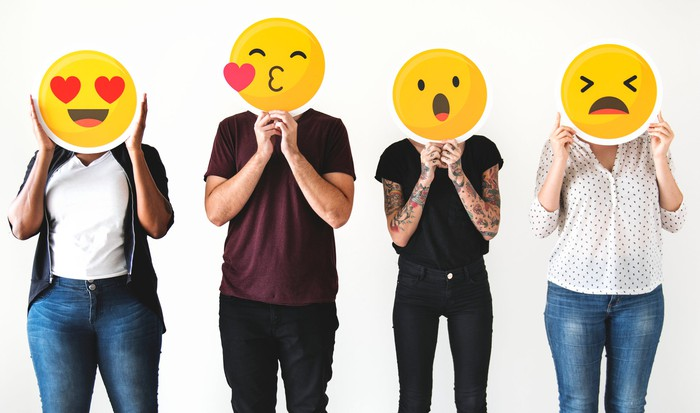 Four people holding common emojis over their faces.