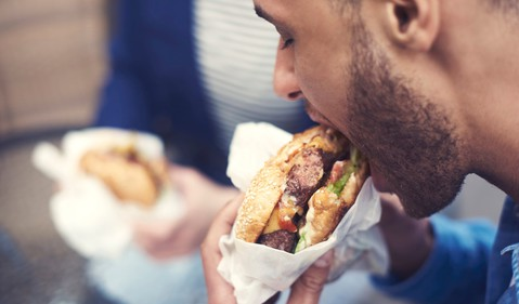 man eating hamburger fast food getty