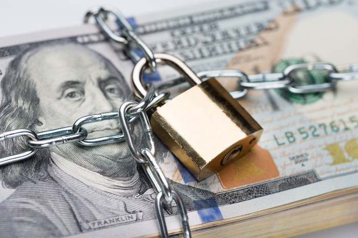 Chain and padlock wrapped around stack of hundred dollar bills.