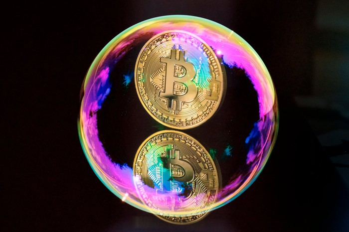 A gold coin with the bitcoin symbol on it, floating in a bubble.