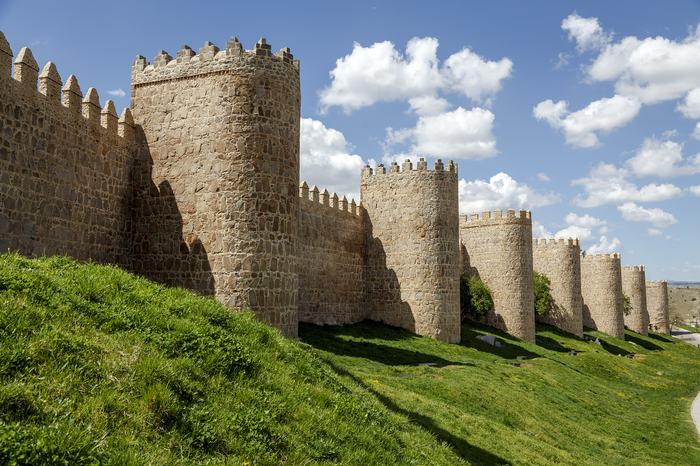 Castle walls casting shadows on green sloping hills. Blue sky with white clouds above.